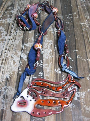 Mother-and-daughter duo Evie and Beth McCord are featured artists this year. They made Warrior Woman, an enameled copper pendant.