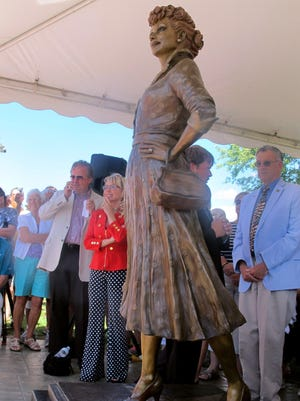 """People gather at the unveiling of the new Lucille Ball statue at Memorial Park in Celoron, the late actress' home town, on Saturday. The statue, by sculptor Carolyn Palmer, replaces a previous statue of the actress that was referred to as """"Scary Lucy."""" The new statue is being shown as part of this year's """"Lucille Ball Comedy Festival."""""""