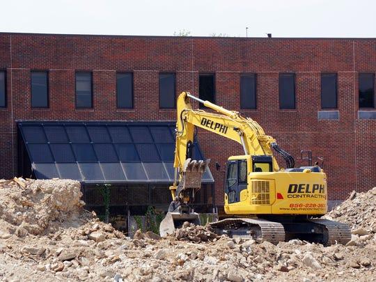 A backhoe moves debris at the Newcomb Hospital demolition