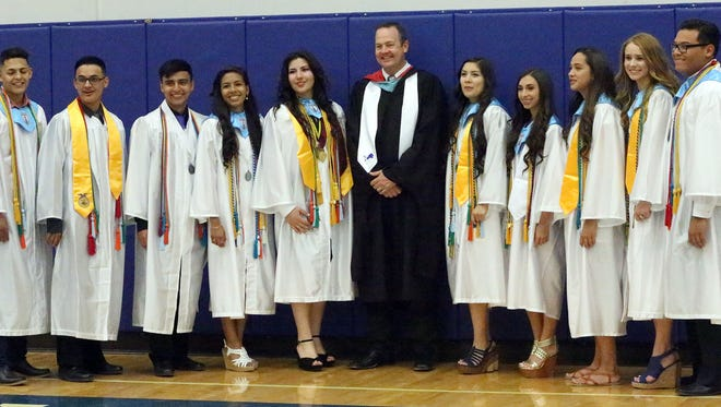 Clint High School principal Garrett Ritchey posts for a photo with the school's top ten from the Class of 2016.