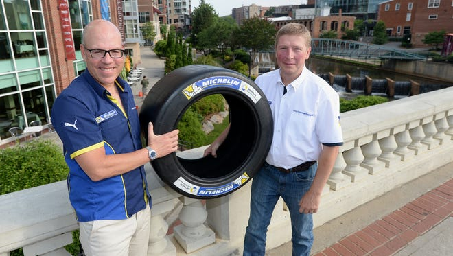 Michelin engineers Lee Willard, left, and John Church pose in downtown Greenville with a Michelin tire. The two will compete for opposing racing teams at Le Mans later this year.