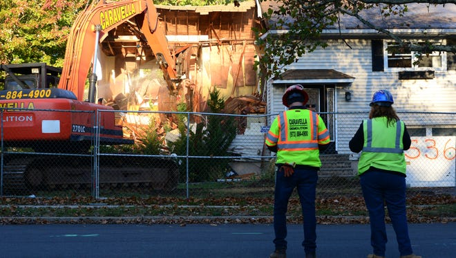 Crews for East Hanover-based Caravella Demolition Inc. watch as a backhoe operator demolishes a flood-prone home on Columbia Street in New Milford on Tuesday.
