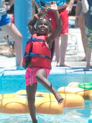 """Jordan Epps, 5, of Stuart, attempts to cross the Wiggly Waters attraction on Wednesday, July 5, 2017, at Sailfish Splash Waterpark in Stuart. """"She's determined. She wouldn't let me tell her no,"""" said Jordan's mother, Jade Thompson (not pictured). In honor of National Park and Recreation Month, all Martin County residents were able to enter the park for free Wednesday. """"It's a celebration,"""" said marketing manager Nancy Johnson. The county-run park hosted cannonball, hula hoop and tube race competitions. For more information, go to www.sailfishsplash.com. To see more photos, go to TCPalm.com."""