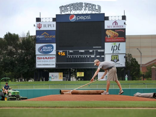 Ten hours before the first pitch, grounds crew and stadium maintenance workers are busy preparing Victory Field for Indianapolis Indians game that night. Here assistant grounds keeper Joey Gerking rakes the pitchers mount. Matt Kryger / The Star