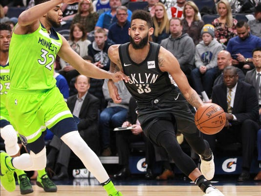 Brooklyn Nets guard Allen Crabbe (33) drives around Minnesota Timberwolves forward Karl-Anthony Towns (32) in the first quarter of an NBA basketball game Saturday, Jan. 27, 2018, in Minneapolis. (AP Photo/Andy Clayton-King)