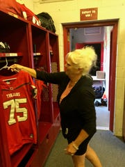 Kristine Baer, a volunteer for Clarenceville's varsity football team, hangs player jerseys up in the locker room before a recent practice.