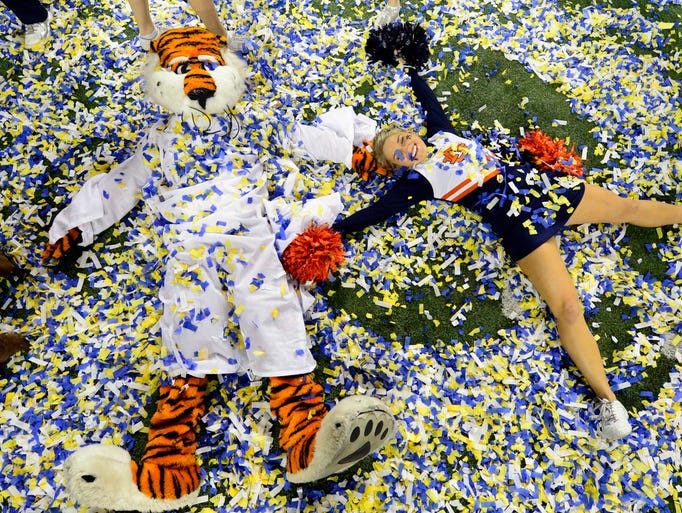 The Auburn Tigers mascot and cheerleader Lauren Lynch play in confetti after defeating the Missouri Tigers in the 2013 SEC Championship game at Georgia Dome.