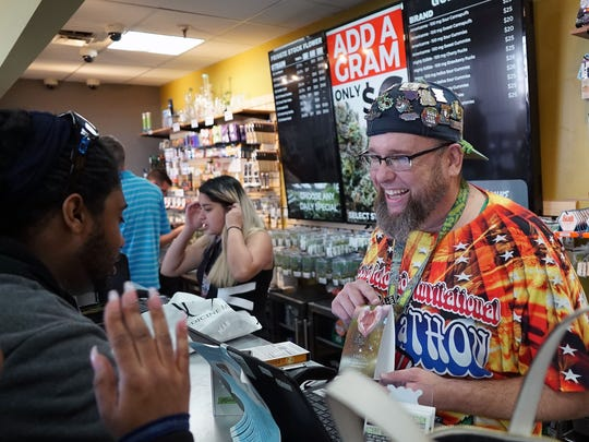 "A ""budtender"" at Denver's Medicine Man marijuana store helps customers with their purchase. Experts say they're not sure how widespread access to high-quality marijuana may change American society."