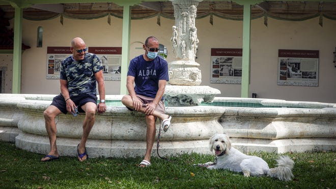 Palm Beach resident Adriano Cerasaro (L) and his friend Nicola Lavacca hang out in Bradley Park with Luna, a goldendoodle, as parks reopened last week for public use after being shut down in response to the coronavirus.