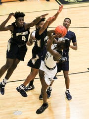 Spartanburg center Adrian Briscoe, left, and guard Talon Cooper defend T.L.Hanna sophomore guard Ja'Hiem Handy during the third quarter on Saturday at T.L. Hanna High School in Anderson. Handy made the shot and was fouled. T.L. Hanna won 66-52.