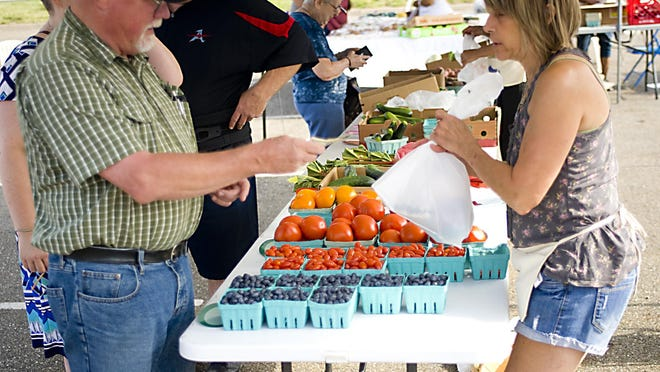 Bob Akins purchases some vegetables from Stephanie Pasztor of Stephanie's Produce during the opening day event of the 2019 Alliance farmers' market.