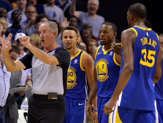 Referee Scott Wall, left, calls Golden State Warriors