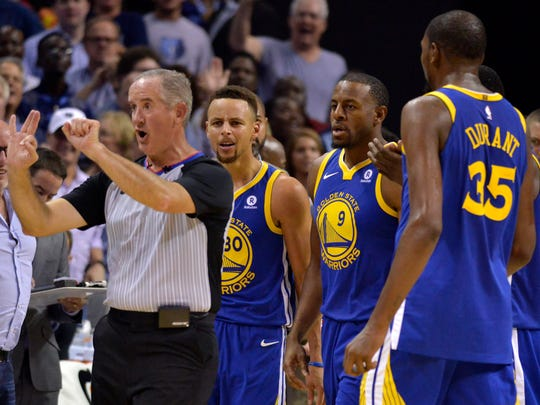 Referee Scott Wall, left, calls Golden State Warriors guard Stephen Curry (30) for a foul as Curry and Warriors forwards Andre Iguodala (9), and Kevin Durant (35) react during the second half of an NBA basketball game Saturday, Oct. 21, 2017, in Memphis, Tenn. Curry and Durant were ejected after arguing with Wall over the call.
