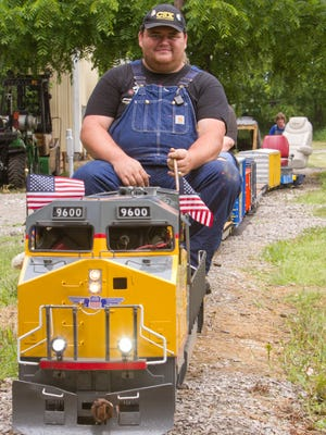 Dan Kalis of Howell Township offers train rides on a 7.5 gauge miniature train setup in the family's back yard. Kalis fires up his gas powered locomotive with passenger cars in tow Wednesday, June 27, 2018.
