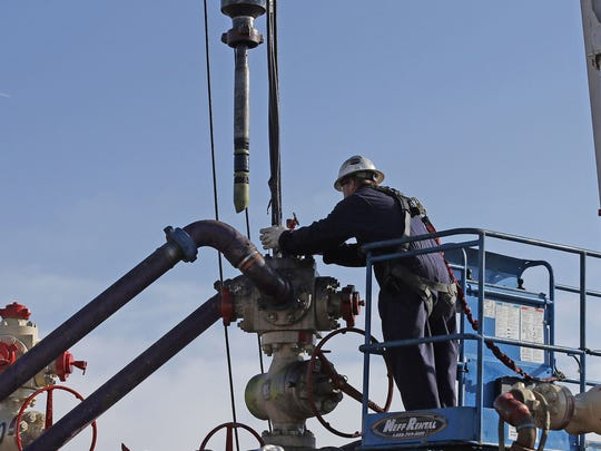 A worker adjusts machinery used for hydraulic fracturing.