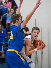 Richmond sophomore Chase Churchill looks to pass around Imlay City junior Griffin Schirmer during a basketball game Friday, Jan. 29, 2016 at Richmond High School.