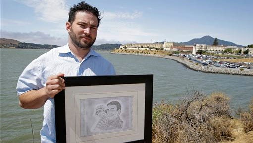 In this photo, Dan Ager holds a graphite sketch showing his father, Alan Ager, and him, while standing outside San Quentin State Prison in San Quentin, Calif. Alan Ager was killed in 2010 at Salinas Valley State Prison and also served time in San Quentin. California state prison inmates are killed at a rate that is double the national average, and sex offenders like Alan Ager account for a disproportionate number of victims, according to an Associated Press analysis of corrections records.