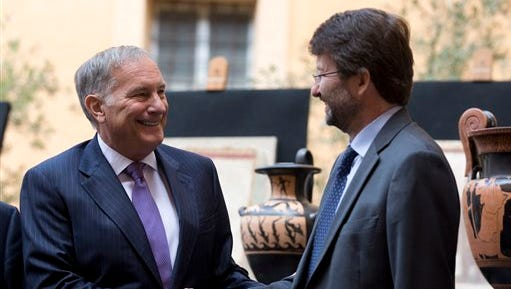 US Ambassador to Italy John Phillip, left, and Italian Culture Minister Dario Franceschini shake hands for photographers at the end of press conference to present ancient artifacts returned to Italy by The United States, in Rome, Tuesday, May 26, 2015. The United States has returned 25 artifacts that were looted from Italy, including Etruscan vases, 1st century frescoes and precious books that had made their way into top-notch U.S. museum, university and private collections. (AP Photo/Alessandra Tarantino)