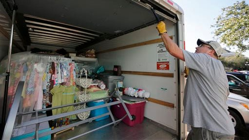 Johnny Osborne closes the door on a moving truck full of items from his store, Dodddlebugs, before high tide hits historic downtown Georgetown, S.C., Thursday, Oct. 8, 2015. Gov. Nikki Haley held a press conference telling Georgetown residents to prepare for floodwaters. Many store owners in the historic district have prepared for repeated flooding over the course of a week. Doddlebugs owners had just finished moving everything back into the store, when they heard the governors press conference and started packing up again. (AP Photo/Mic Smith)