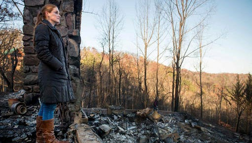 Veronica Carney looks at the skyline from the remains of the home she grew up in, Thursday, Dec. 1, 2016, in Gatlinburg, Tenn. Carney flew in from Massachusetts to assist her parents, Richard T. Ramsey and Sue Ramsey who safely evacuated as a wildfire approached Monday evening.