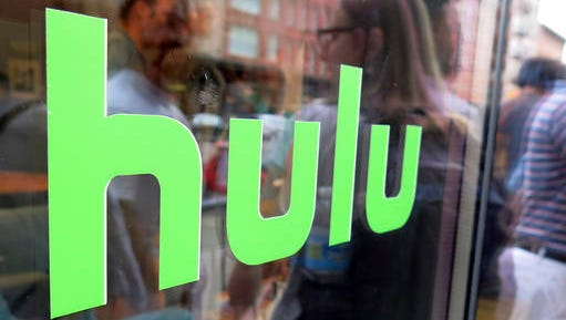 FILE - This June 27, 2015, file photo, shows the Hulu logo on a window at the Milk Studios space in New York. Hulu says it signed a deal with CBS Corp. to add three of the media company's channels to its upcoming live TV streaming service. The deal will give Hulu the right to live stream the nation's most-watched broadcast network -- CBS -- as well as CBS Sports Network and cable channel Pop.
