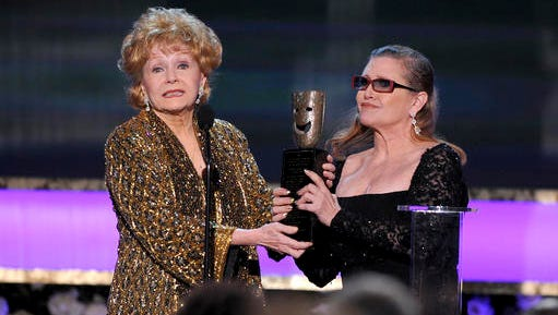 FILE- In this Jan. 25, 2015, file photo, Carrie Fisher, right, presents her mother Debbie Reynolds with the Screen Actors Guild life achievement award at the 21st annual Screen Actors Guild Awards in Los Angeles. Reynolds' death certificate obtained Tuesday, Jan. 10, confirms that the actress died of a stroke.