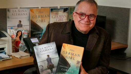 """Armando Correa, Editor in Chief of People en Espanol, poses with the Spanish and English versions of his novel, """"The German Girl,"""" in his office in New York, Tuesday, Jan. 24, 2017."""