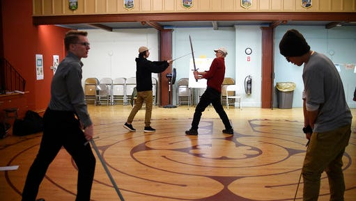 """In this Thursday, March 2, 2017 photo, Kevin Coleman, right rear, director of education at Shakespeare & Co., works with a teenage man, left rear, playing the role of a soldier, as another young man, left front, portraying Macbeth, practices a sword fight with another young man, right front, portraying Macduff during a rehearsal for Shakespeare's """"Macbeth,"""" in Pittsfield, Mass. Shakespeare & Company, a theater company in Lenox, Massachusetts, works with the courts to get youngsters who run afoul of the law sentenced to perform works of Shakespeare onstage as an alternative to community service or juvenile detention."""