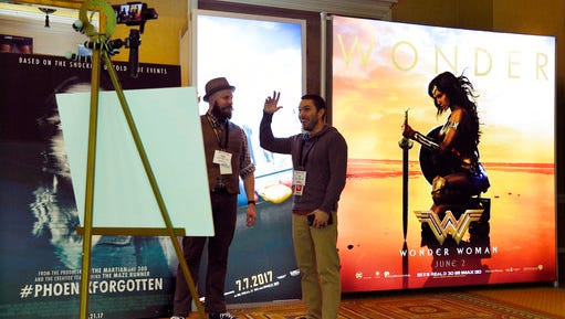 "Drew Lawrence, left, and Joey Paur film a segment for their web show ""Geek Tyrant"" in front of an advertisement for the upcoming film ""Wonder Woman"" during CinemaCon 2017 at Caesars Palace on Monday, March 27, 2017, in Las Vegas."