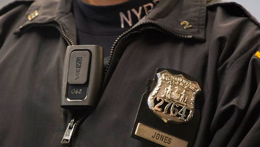 FILE - In this Dec. 3, 2014 file photo, New York Police Department officer Joshua Jones wears a VieVu body camera on his chest during a news conference in New York. The NYPD, the nation's largest police department, will begin rolling out body cameras by the end of this month, after resolving the thorniest issues on when to turn them on and off, and how long video will be kept.