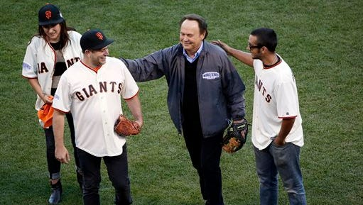 Robin Williams son, Zak Williams, second from left, gets a pat on the back from Billy Crystal after Zak threw out the ceremonial first pitch as his siblings Zelda, left, and Cody look on before Game 5 of baseball's World Series between the Kansas City Royals and the San Francisco Giants on Sunday in San Francisco.
