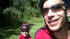 Ron Plush, right, with his son, Kyle, riding bicycles
