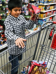 Osvaldo Espinola, 6, picks toys on a shopping spree for the Concho Valley Home for Girls/Children's Emergency Shelter on Tuesday, Dec. 19, at San Angelo H-E-B #2.