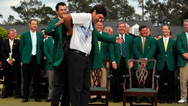 2013 winner Adam Scott (left) helps 2014 winner Bubba Watson into a green jacket after the the Masters golf tournament at Augusta National Golf Club.