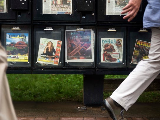 People walk past a Knoxville Mercury box on Gay Street