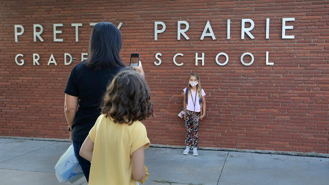 Kimberly Detter takes photos of her daughter, Lila Detter, 7, on her first day of second grade Wednesday morning at Pretty Prairie Grade School, with fifth-grade daughter Lauren Detter looking from behind her. The grade school is for students in kindergarten through fourth grade.