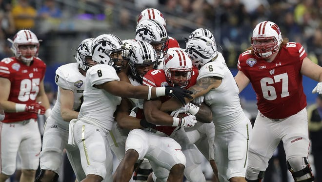 Asantay Brown #6 and Caleb Bailey #8 of the Western Michigan Broncos tackle Sojourn Shelton #8 of the Wisconsin Badgers inthe third quarter during the 81st Goodyear Cotton Bowl Classic between Western Michigan and Wisconsin at AT&T Stadium on January 2, 2017 in Arlington, Texas.