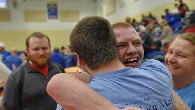 Blue Ridge senior Christian Mills is hugged by his brother, Jordan, and mother, Christi, as Tigers coach Austin Weathers looks on after Mills qualified for state at 182 pounds during Saturday's Class AAAA Upper State tournament at Eastside High School.