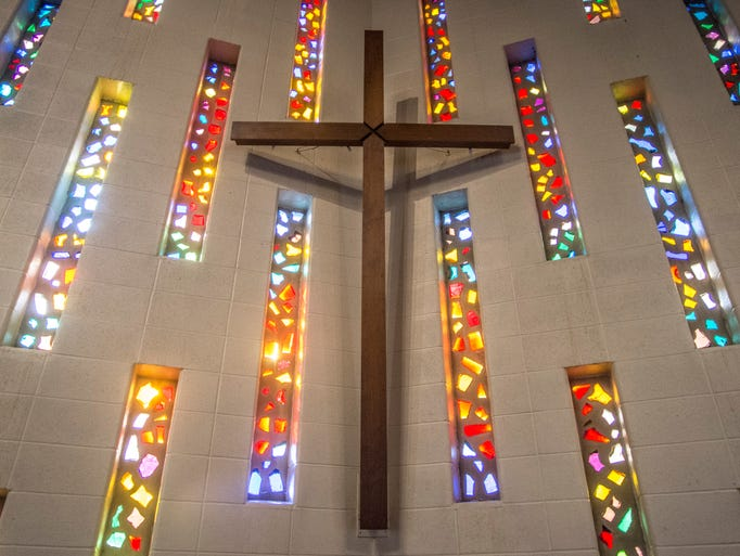 A cross hangs on the south wall of the sanctuary at