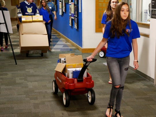 Daniela Olt, 15, of 'Daniela's Wish' pulls a cart load of toys to be delivered to children at the K. Hovnanian Children's Hospital, Monday, August 7, 2017.  She was assisted by New Jersey State Policemen's Benevolent Association Hockey team members.