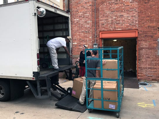 Workers load dozens of boxes of merchandise from the