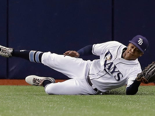 Tampa Bay Rays center fielder Mallex Smith slides across the turf after making a catch on a fly-out by Milwaukee Brewers' Domingo Santana during the first inning of a baseball game Saturday, Aug. 5, 2017, in St. Petersburg, Fla. (AP Photo/Chris O'Meara)