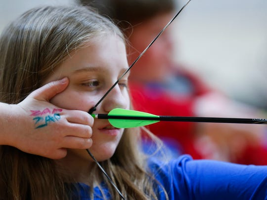 Heather Lyons, 13, from Pipkin Middle School, pulls back on a bow string to launch an arrow towards a target during practice for an archery competition at the O'Reilly-Tefft Gymnasium on Tuesday, Jan. 9, 2018. About 700 Springfield middle school and high school students are competing in the district's first official archery competition.