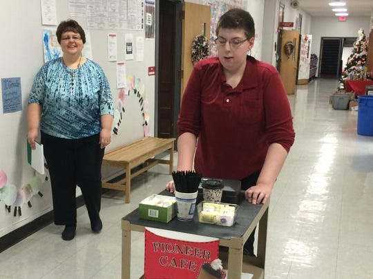 Liam Behme, a Sevastopol eighth-grade student, pushes a cart of coffee during morning deliveries. Liam is one of four students who work in the school's Pioneer Café. Accompanying him is Sevastopol's special education teacher, Leann Leonardson.