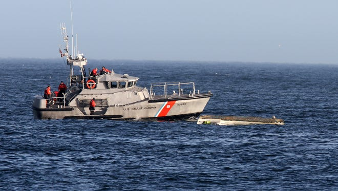 A U.S. Coast Guard boat cruises past a capsized boat close to the Manasquan Inlet around 2:30 p.m. in Manasquan Friday.