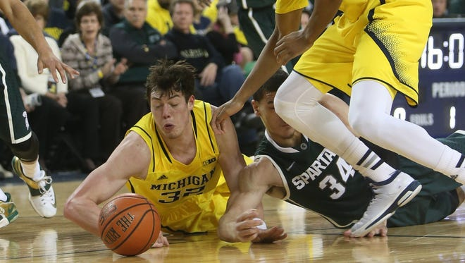 Michigan's Ricky Doyle goes for a rebound against Michigan State's Gavin Schiiling during first half action on Tuesday, February 17, 2015 at Crisler Center in Ann Arbor.