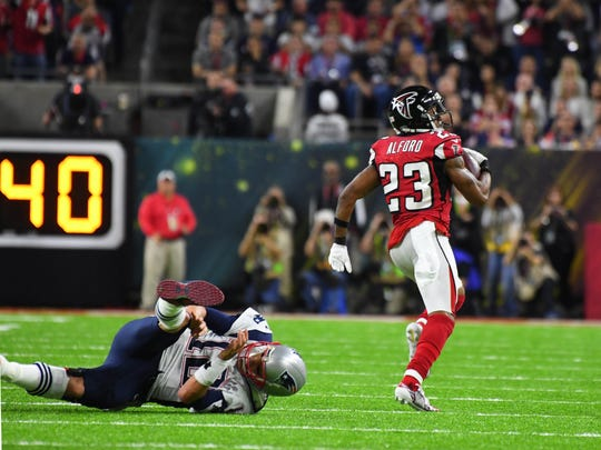 Atlanta Falcons cornerback Robert Alford scores a touchdown on an interception return after avoiding New England Patriots quarterback Tom Bradyin the second quarter during Super Bowl LI at NRG Stadium.