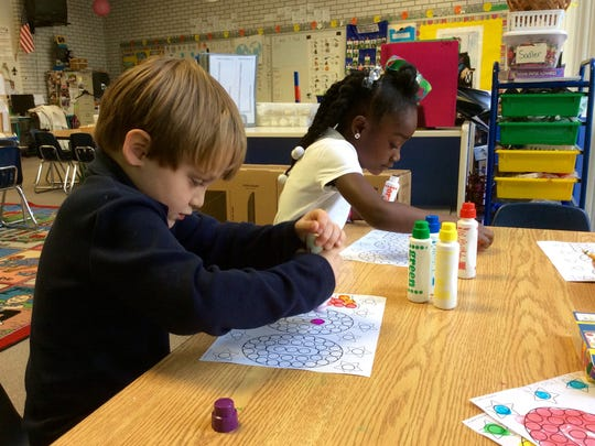 "Landon Bordelon and Atarah Robinson, pre-K and kindergarten students in Jolie Sadler's class at Peabody Montessori Elementary School, ""dot to 100"" Monday as part of their 100th day of school celebration. Kids worked in pairs in centers completing activities with the 100-day theme."