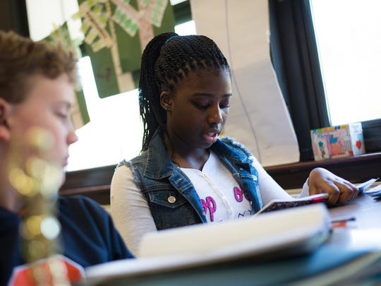 Ka'Mia Edwards, 11, reads her piece out loud for the class at the end of a writing workshop.