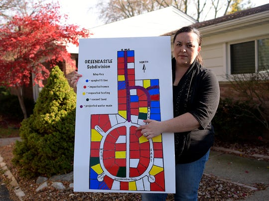 Resident Melanie Williams poses for a photo with a poster she made. Some 48 houses marked red are impacted.